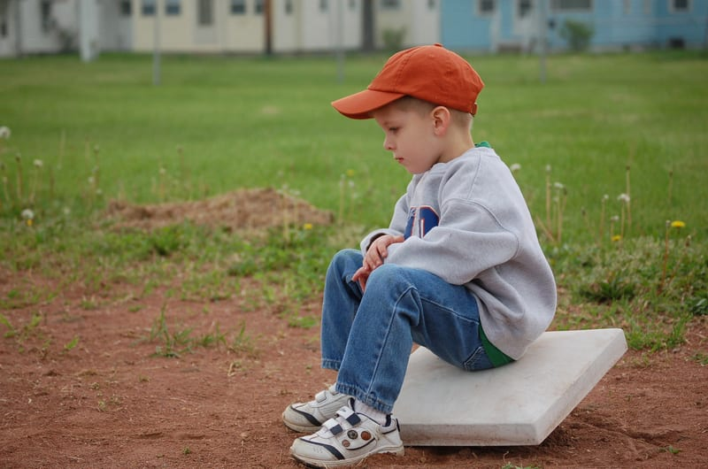 boy sitting on baseball base - Late Talkers Foundation
